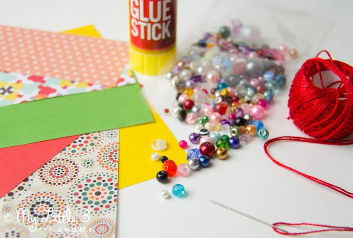 Have fun with paper & beads to make adorable homemade Christmas ornaments. Our paper tree decorations are so simple and pretty and great for children to enjoy making too!