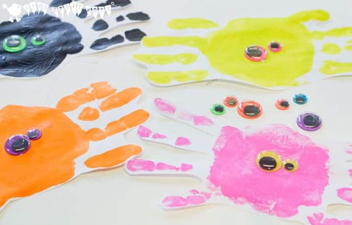 Adding features to cute handprint spiders. Handprint Spiders In Webs are easy & frugal to make and a super way to build fine motor threading skills. A fun spider craft for Halloween & all year round.