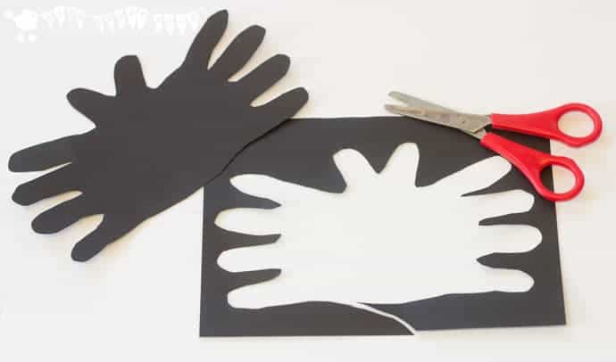 Cutting out the template for a cute and cheeky Halloween Bat handprint craft for kids.