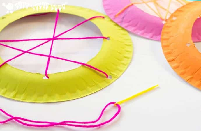 Weaving Paper plate Webs - Handprint Spiders In Webs are easy & frugal to make and a super way to build fine motor threading skills. A fun spider craft for Halloween & all year round.
