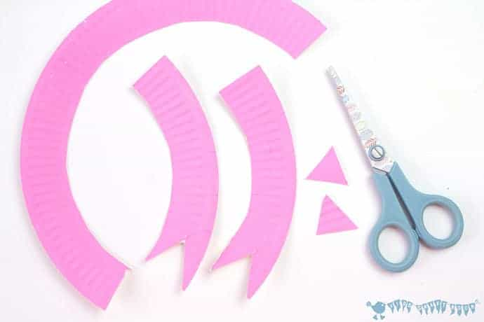 cutting-paper-plates-to-make-paper-plate-rosette-ribbons-for-grandparents-day-craft