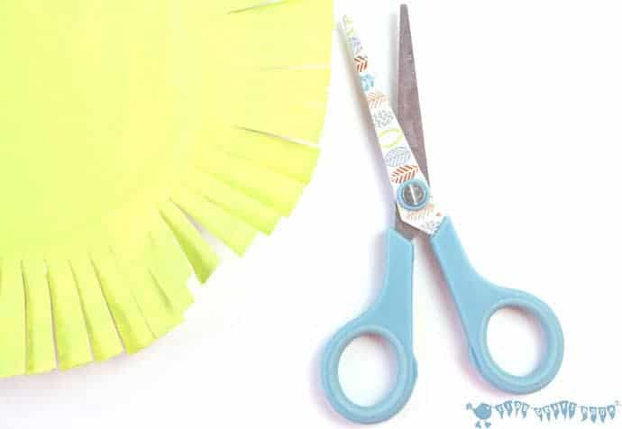 cutting-paper-plates-to-make-paper-plate-rosettes-grandparents-day-craft