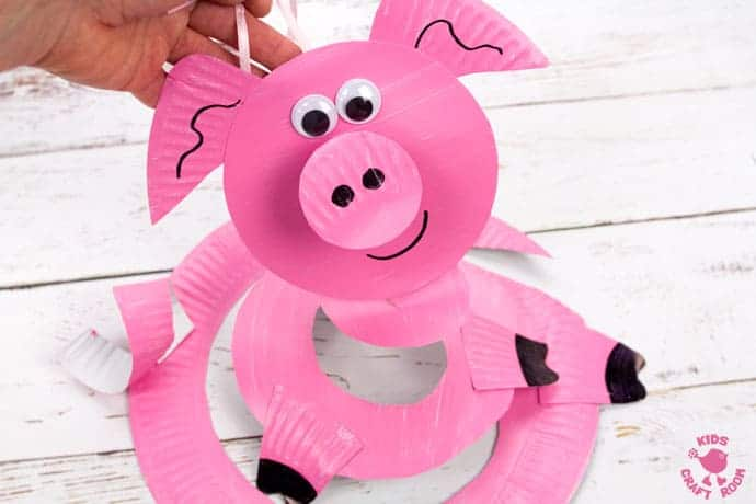 This Paper Plate Pig Twirler is adorable! A simple pig craft that's really quick and easy to make. Hold your pig twirler craft up and give it a blow to see it spin round and round. Such a fun paper plate craft for kids. Great for farm animal themes and Chinese year of the pig. #kidscraftroom #pigcrafts #pigs #paperplates #paperplatecrafts #twirlers #whirligigs #preschoolcrafts #toddlercrafts