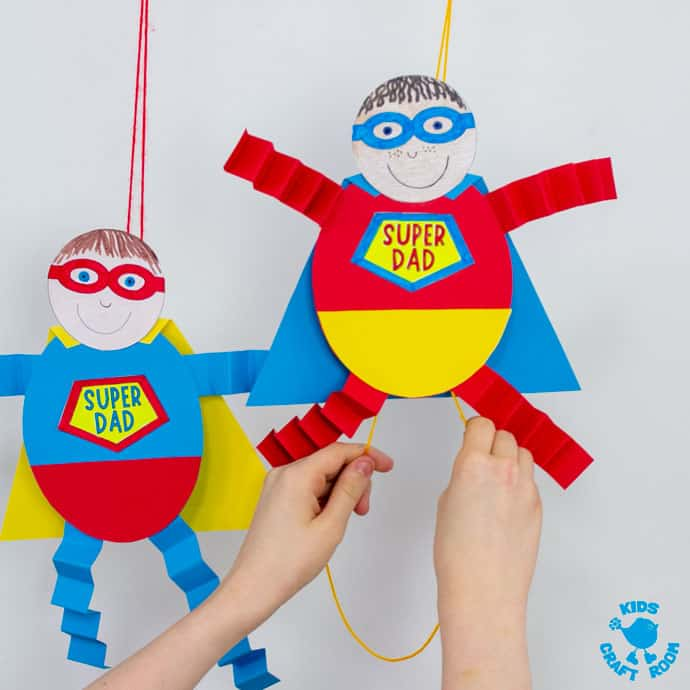 Two suspended Father's Day Flying Super Dad craft with child's hands pulling the strings of one to make it fly.