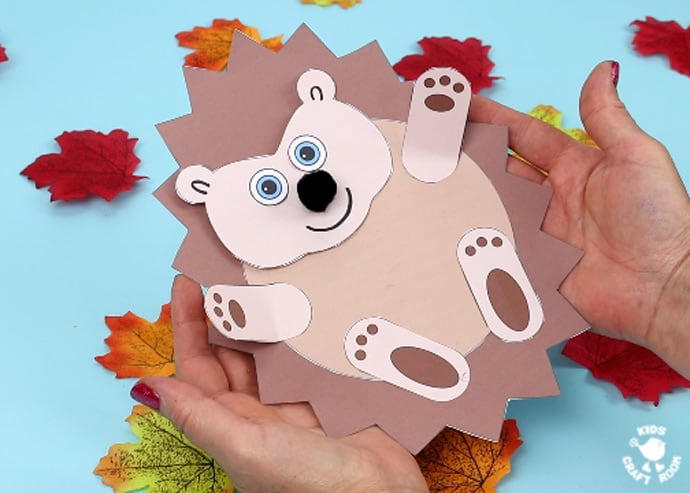 Moving Baby Hedgehog Craft lying in open hands with a background of leaves.