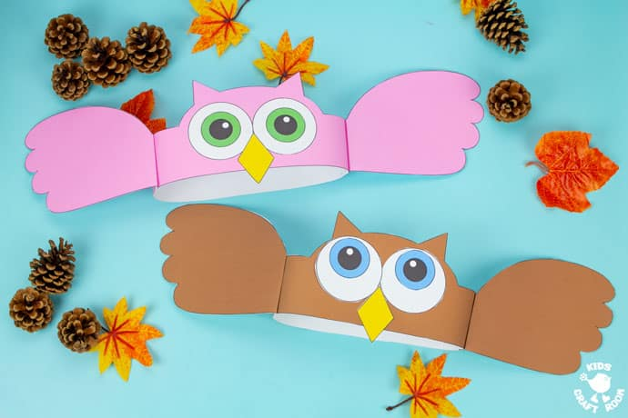 Owl Hat Craft in pink and brown on a blue tabletop with pinecones and leaves scattered around them.