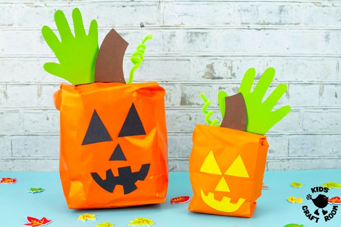 Handprint and Paper Bag Pumpkins on a blue table top.