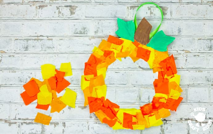 Paper Plate Pumpkin Wreath Craft on a white brick wall.
